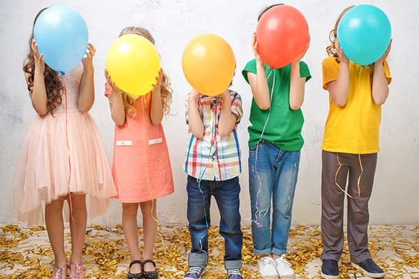 images of children holding balloons in front of their face