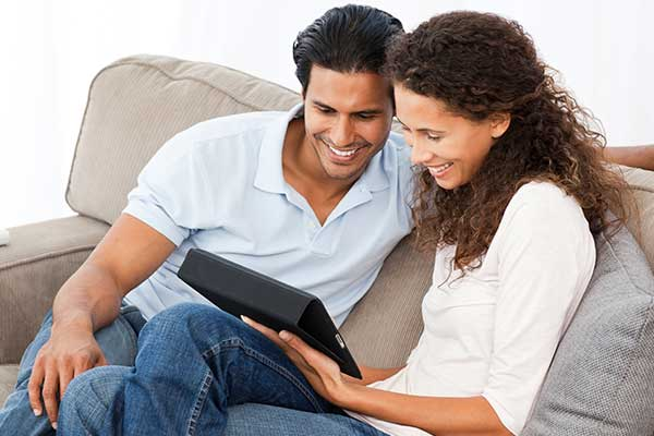 image of a couple looking at their tablet device